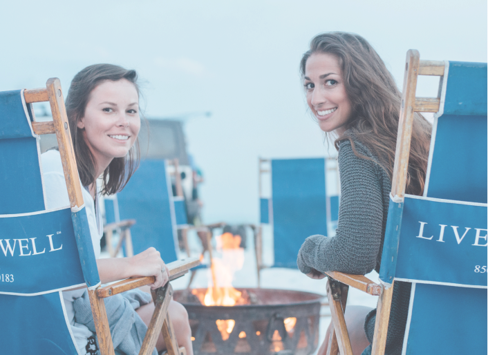 Two women sitting at a bonfire in LiveWell30a beach chairs.