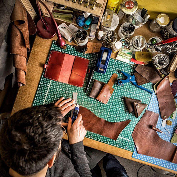 A man in a leather workshop seen from above while working on the products