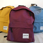 A Picture of all three of our heritage Backpacks, each featuring a branded woven patch. From left to Right: Heritage Backpack in Mustard Yellow, Heritage Backpack in Burgundy and The Heritage backpack in Airforce Blue