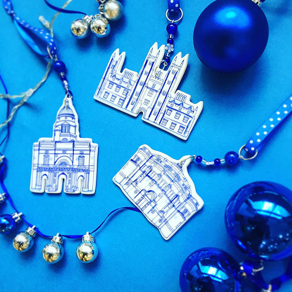 Three different ceramic decoration on a blue background, featuring Old College, New College and McEwan Hall