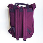 A picture of the back of the Roll Top backpack in Burgundy displaying two padded shoulder straps.