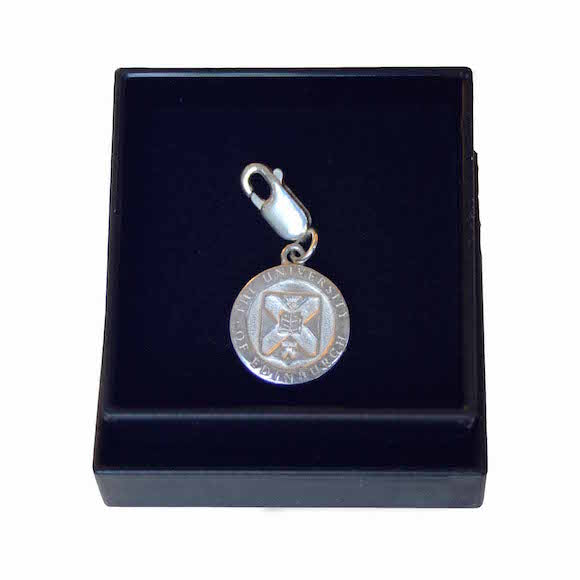 A silver charm featuring the Edinburgh University Crest