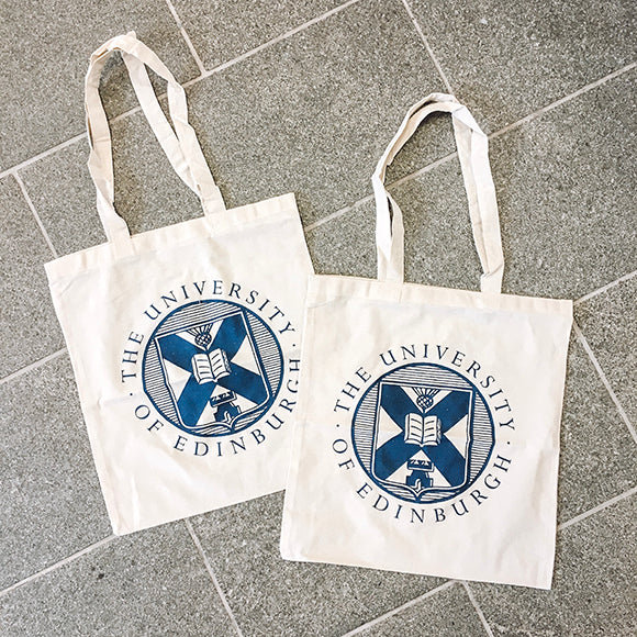 Two white cotton totes both featuring the Edinburgh University crest in navy blue.