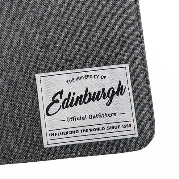 Close up of the woven branded patch which reads ' The University of Edinburgh, Official Outfitters, Influencing the World Since 1583'