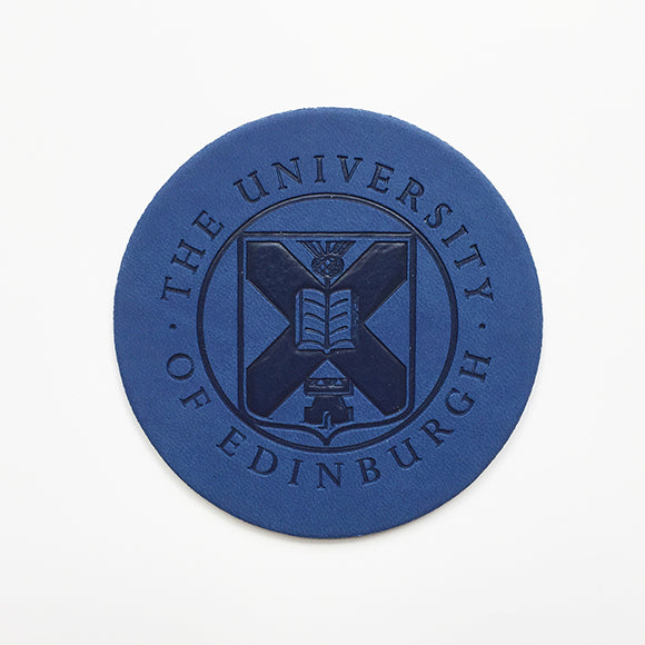 Front view of a leather coaster with embossed University crest in blue