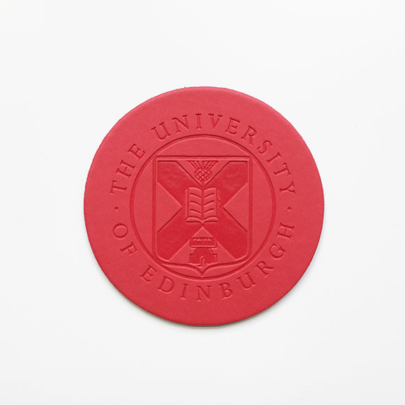 Front view of a leather coaster with embossed University crest in red
