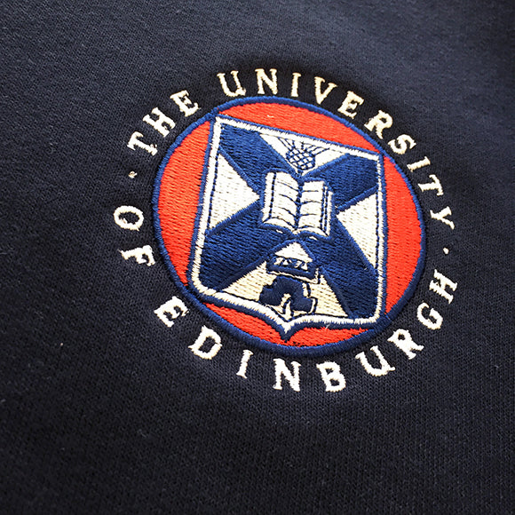 Detail of the classic University of Edinburgh logo embroidered on our navy sweatshirt. This embroidered logo features the classic University of Edinburgh colours: white, red and navy. The words 'The University of Edinburgh' in white circling the University of Edinburgh crest.