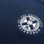 Close up of white University crest on Navy t-shirt