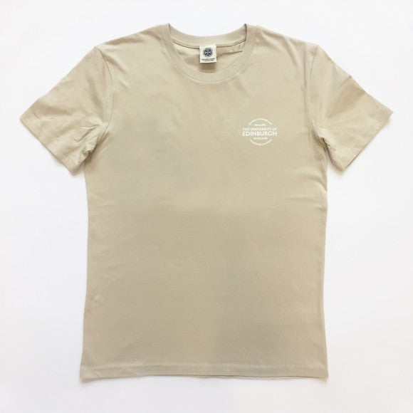 A sand coloured t-shirt with small circular design in white in the top left corner stating the name and year of establishment in English and Gaelic.