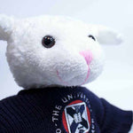 Dolly the Sheep stuffed toy in a sweater featuring the University of Edinburgh crest, close up