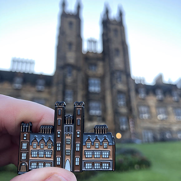New College Pin Badge held against New College