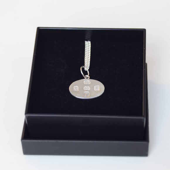 Sterling silver necklace with a silver oval charm with the inlay of the makers hallmark