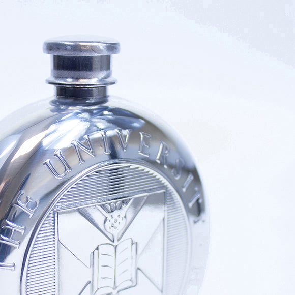 Close up of the embossed University crest on the round pewter hipflask