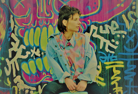 young-woman-sitting-in-front-of-graffiti-wall-creatively-dressed-in-mens-fresh-vintage-wear