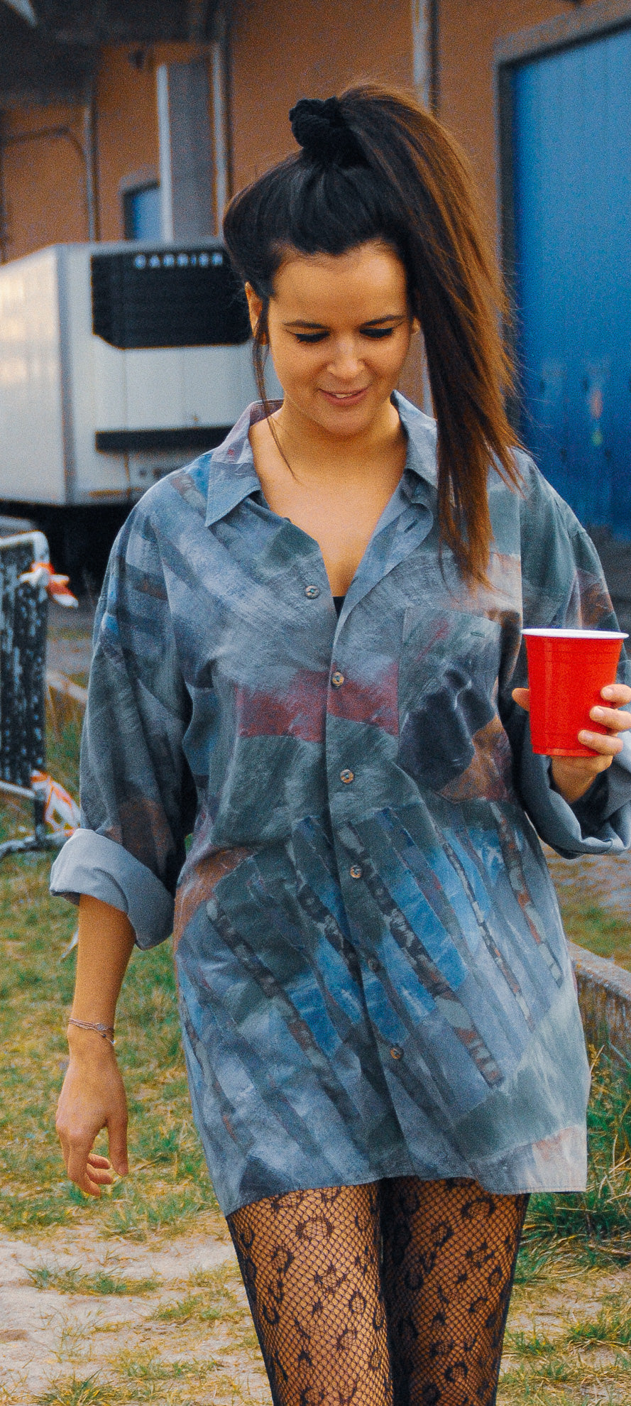 women-wearing-long-vintage-shirt-from-fresh-vintage-collection-in-green-walking-carrying-red-american-drink-cup