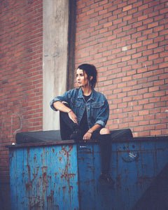 Young-woman-sitting-on-metal-container-wearing-vintage-jeans-jacket-grunge-style