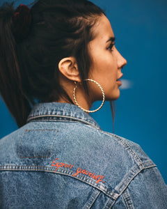 Young-woman-wearing-jeans-jacket-with-embroidery-express-yourself