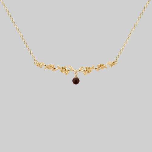 gold floral choker with garnet gemstone