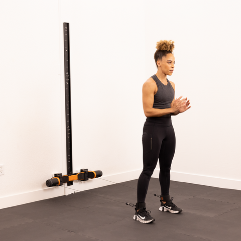 female standing by wall about to workout