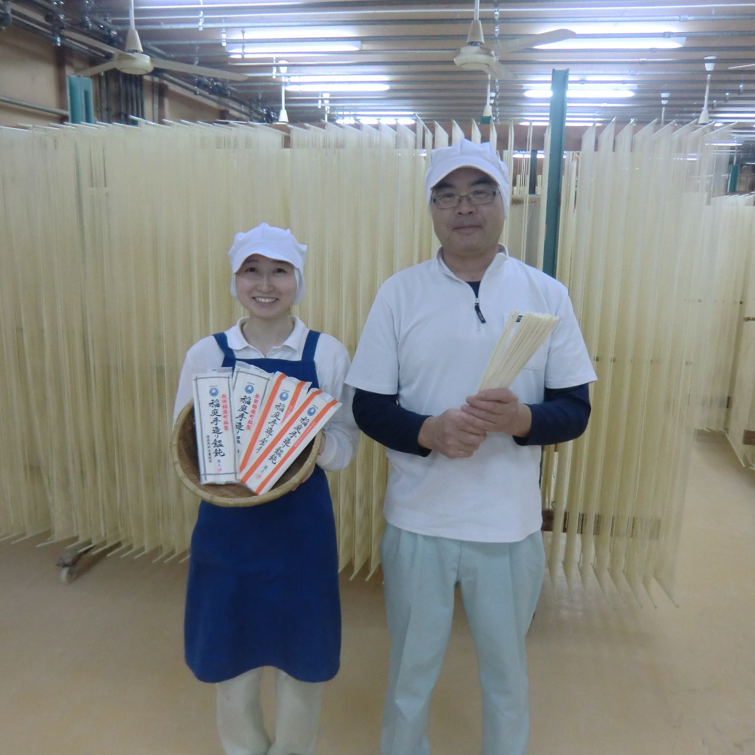 Two craftspeople holding noodles