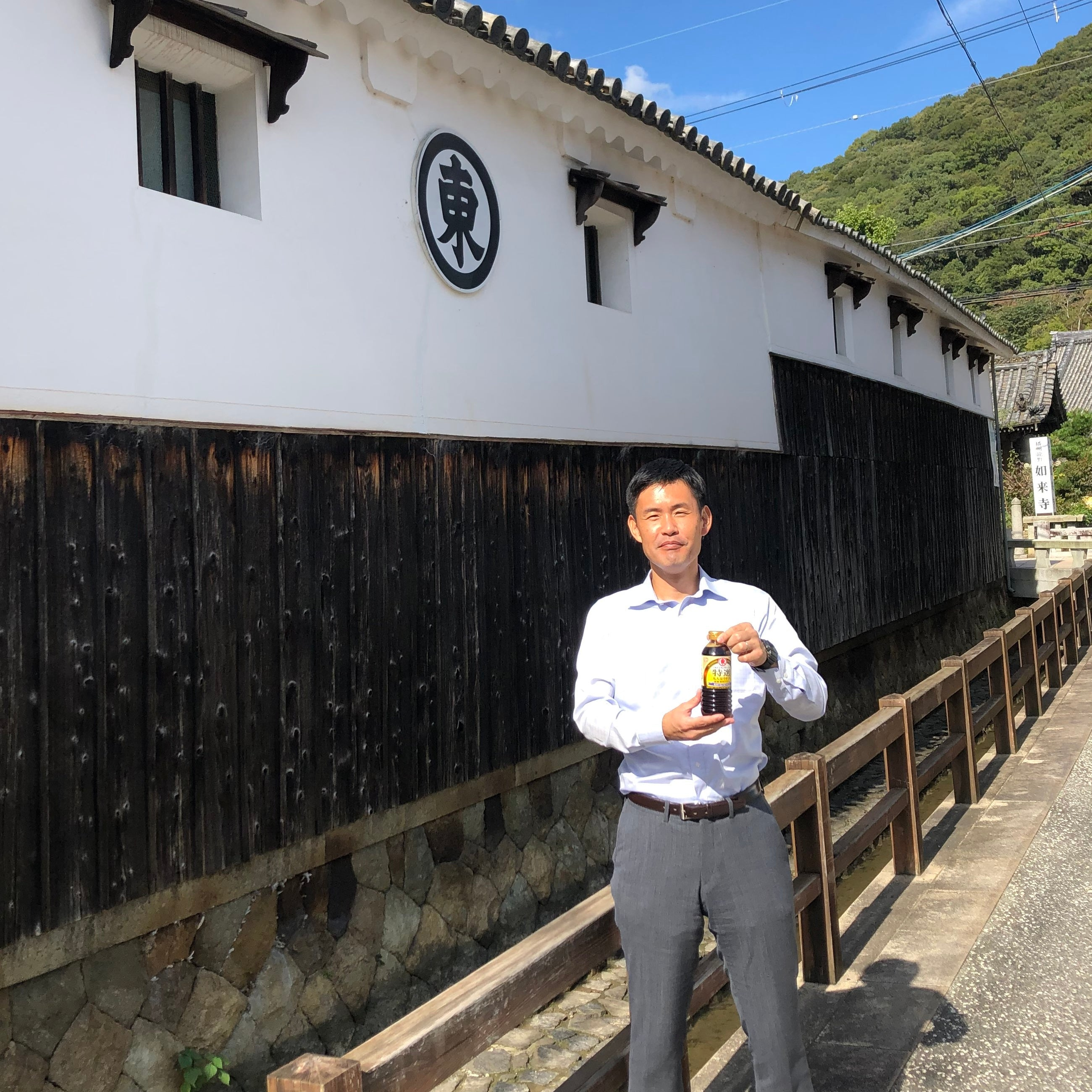 Man holding a bottle of soy sauce in front of factory