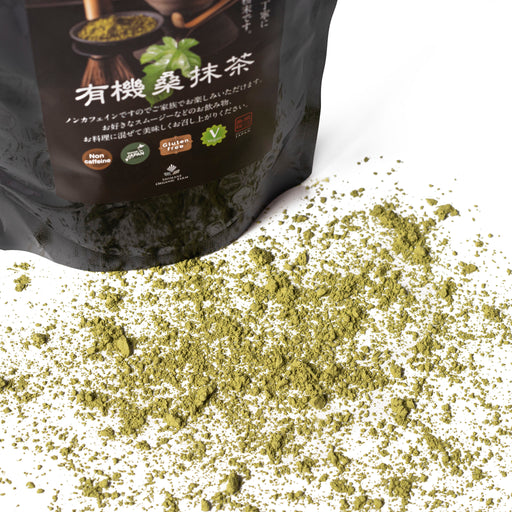 Scattered organic mulberry matcha powder next to package of the product