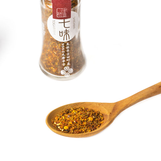 A spoon of shichimi togarashi pepper powder next to bottle of the package
