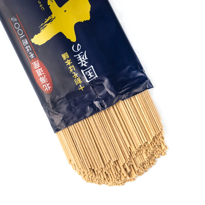 Dried juwari soba noodles popping out of package of the product
