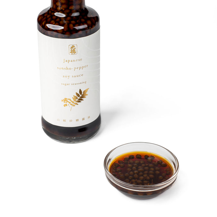 A small glass bowl of sansho pepper soy sauce next to bottle of the product