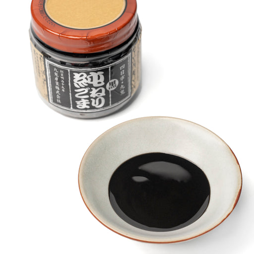A small bowl of black sesame paste next tp bottle of the product