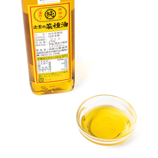 A small bowl of rapeseed oil next to package bottle of the product