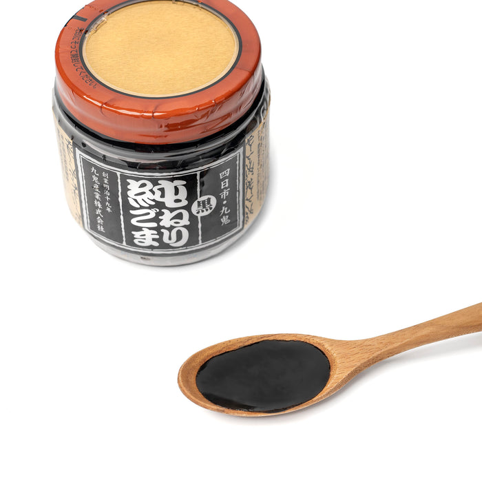 A spoon of black sesame paste next to bottle of the product