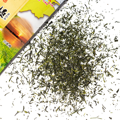 Scattered green tea leaves next to package of the product
