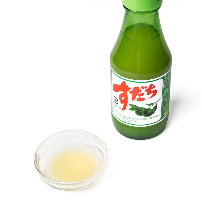 A bowl of sudachi juice next to a bottle of the product