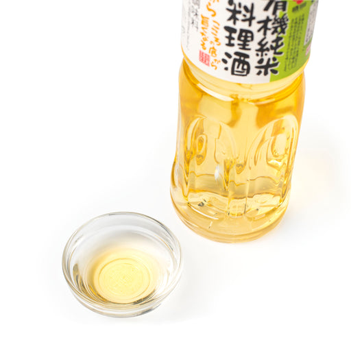 A small bowl of organic cooking sake next to bottle of the product - diagonal angle