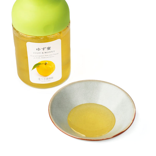 A small bowl of Yuzu Honey next to package bottle of the product