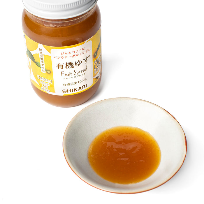 A small bowl of organic yuzu spread next to bottle of the product