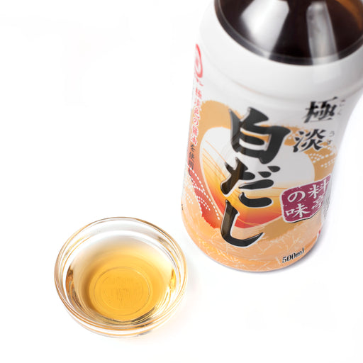 A small bowl of shiro dashi next to bottle of the product