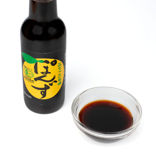 A small bottle of organic ponzu sauce next to bottle of the product