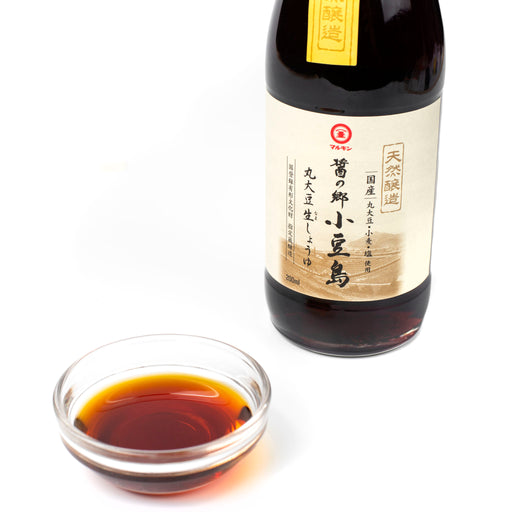 A small bowl of soy sauce next to bottle of the product