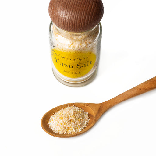 A wooden spoon of yuzu salt next to bottle of the product