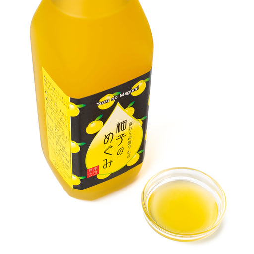 A glass bowl of yuzu syrup next to bottle of the product