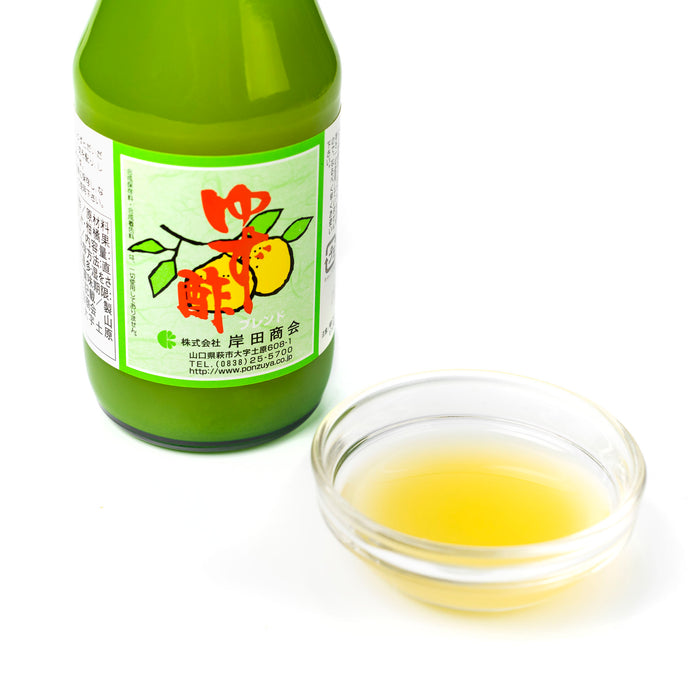 A small glass bowl of yuzu vinegar next to bottle of the product