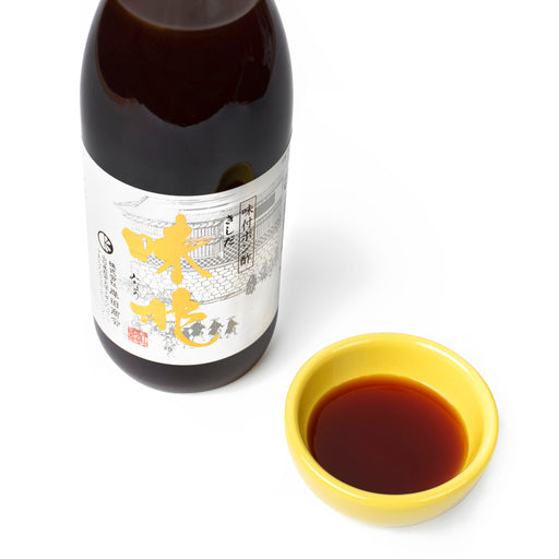 A small bowl of ponzu sauce next to bottle of the product