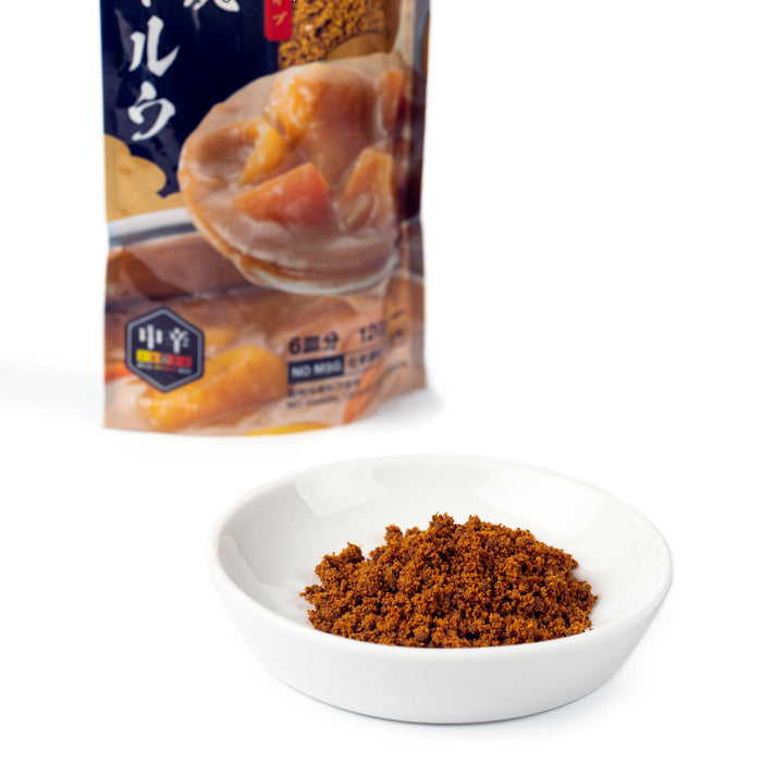 A small bowl of curry roux flakes next to package of the product