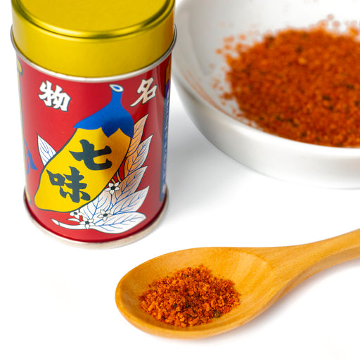 A spoon of shichimi togarashi pepper powder next to a bottle of the product and a bowl of shichimi togarashi pepper powder