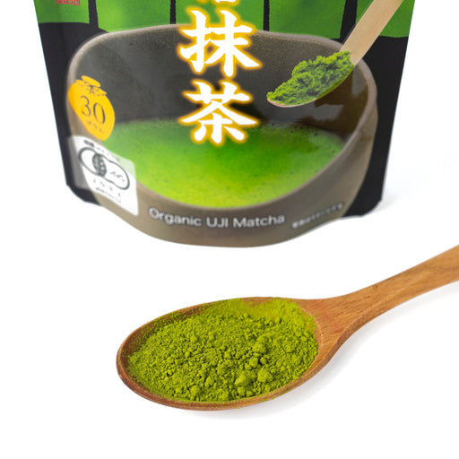 A spoon of the organic matcha powder in front of package of the product