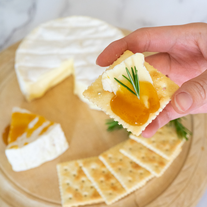 Man taking a piece of cracker topped with cheese and organic yuzu spread by hand