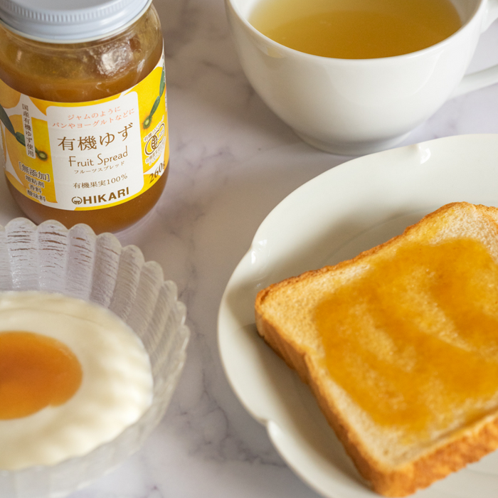 A package bottle of the product surrounded by a slice of bread, a bowl of yogurt, and a cup of tea