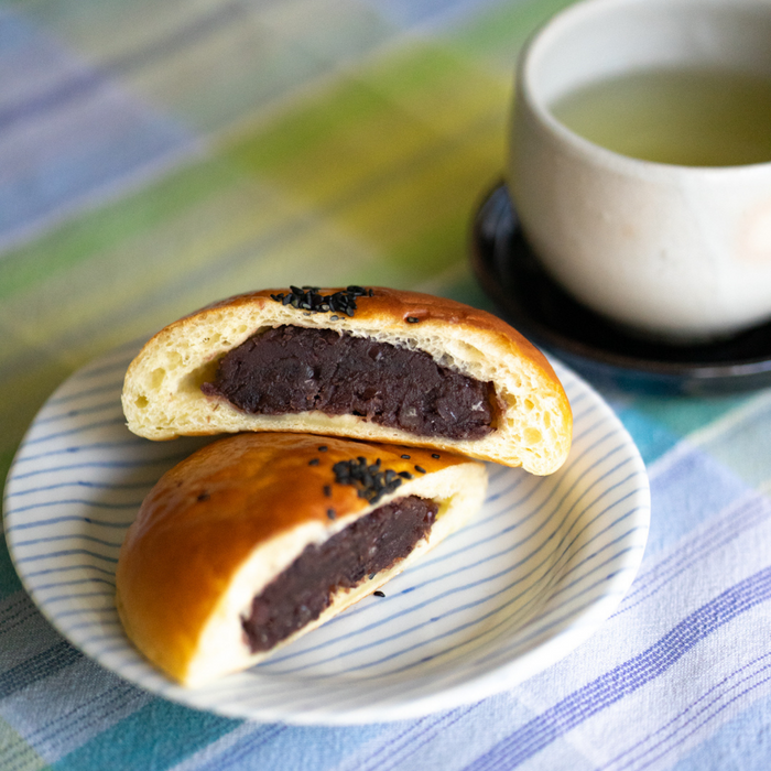 Red bean stuffed bread on a plate next to a cup of tea